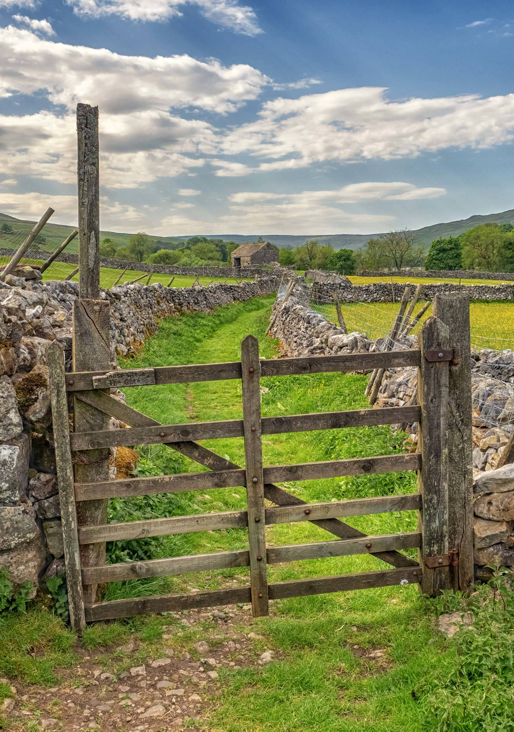 Wooden gate leading to a path between dry stone walls near Morton House in Masham in the Yorkshire Dales
