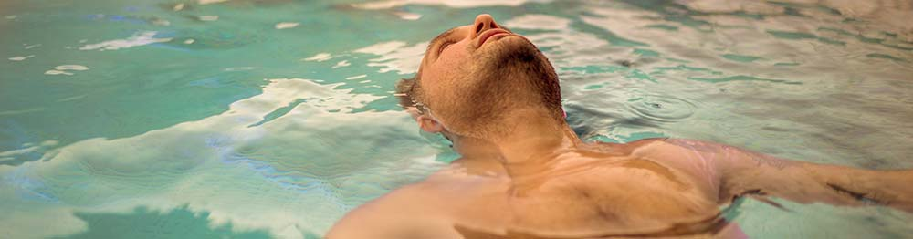 Man floating in water at a spa