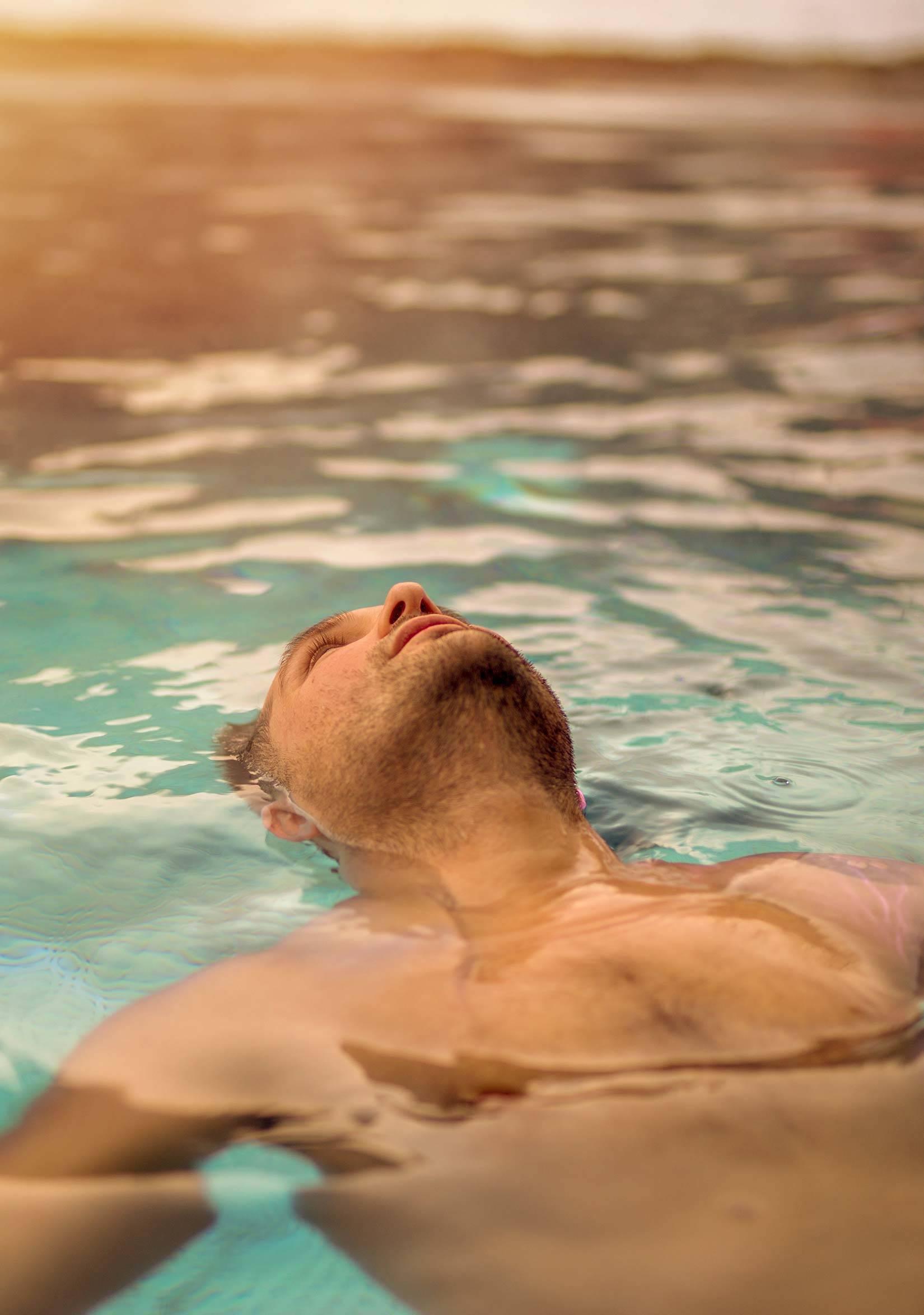 Man floating in pool at spa