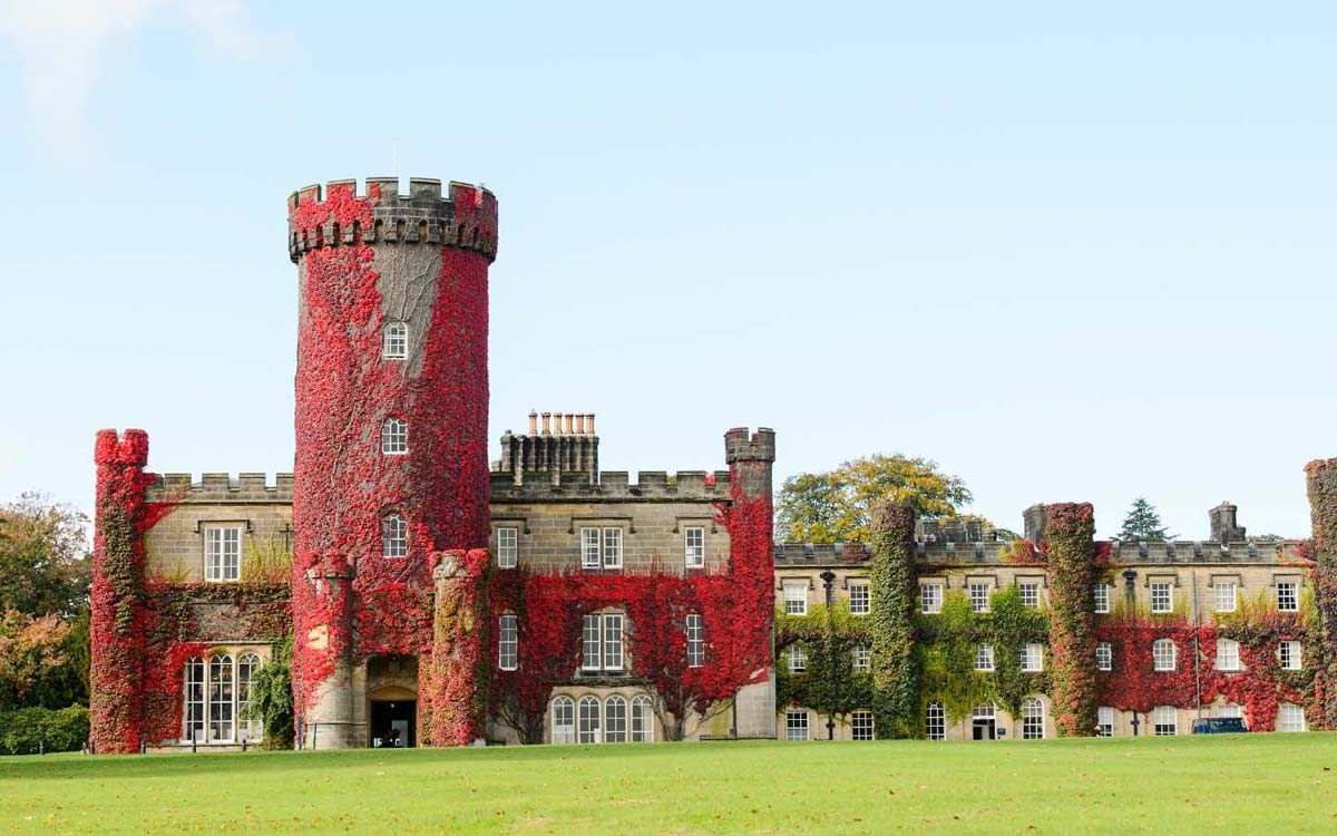 Front facade of Swinton Park in the Autumn covered in red leaves