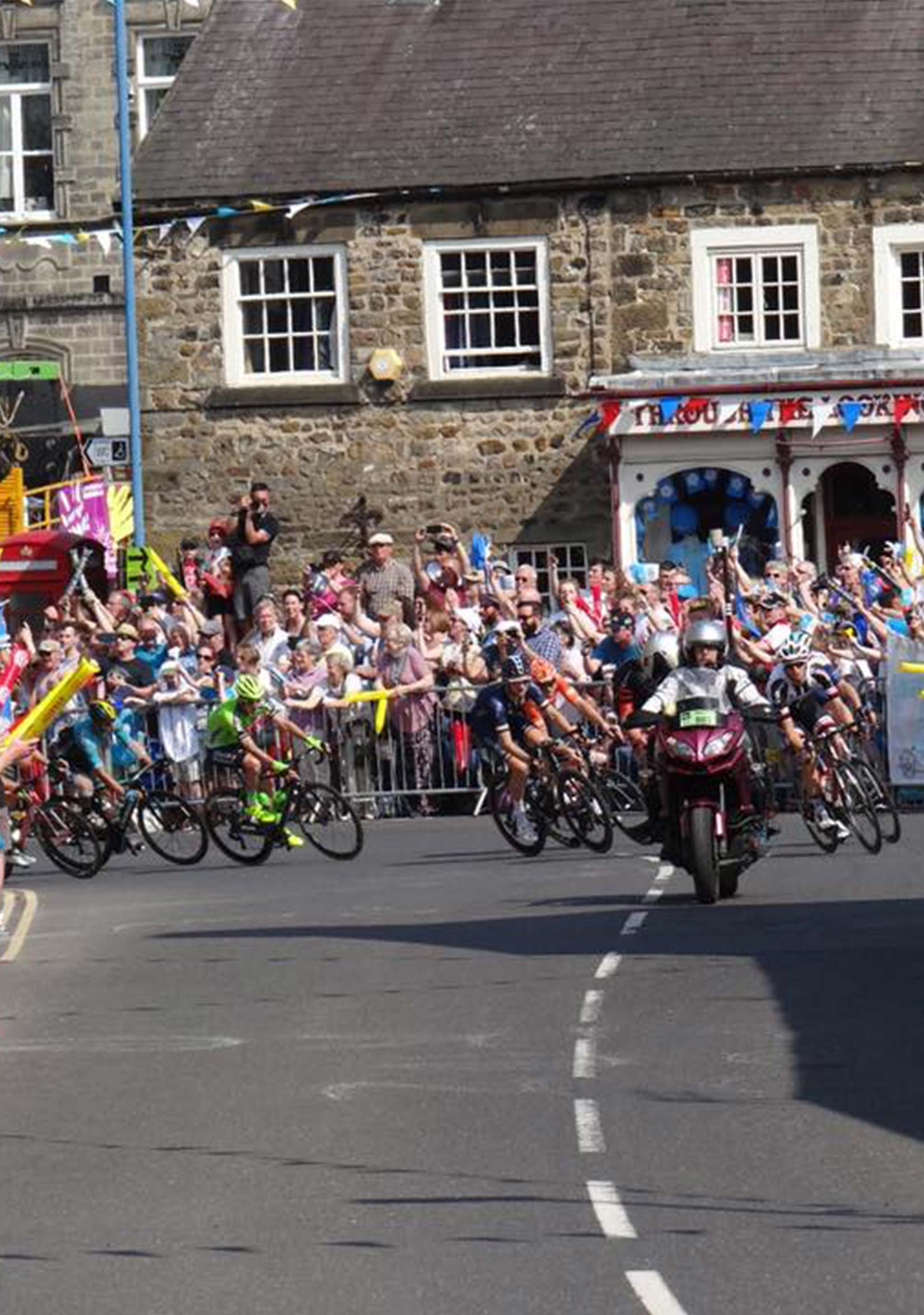 Cyclists on the Tour de Yorkshire cycling through Masham along Silver Street