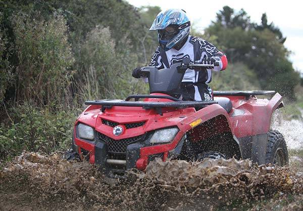 Man on quad bike driving through the mud and dirty water