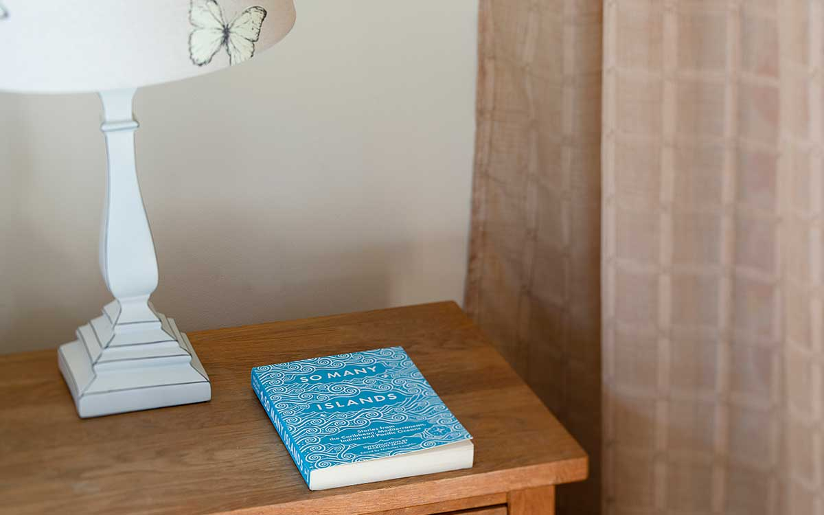 Stable Block decorative detail book beside lamp on bedside table