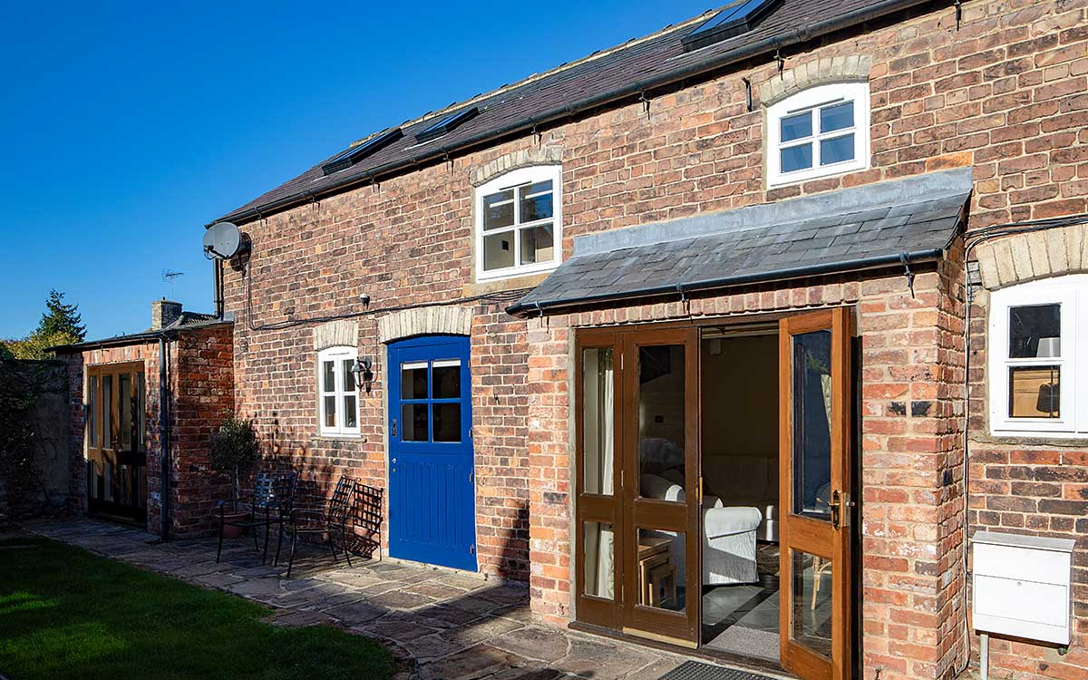 Stable Block exterior with doors open on a sunny day with a blue sky